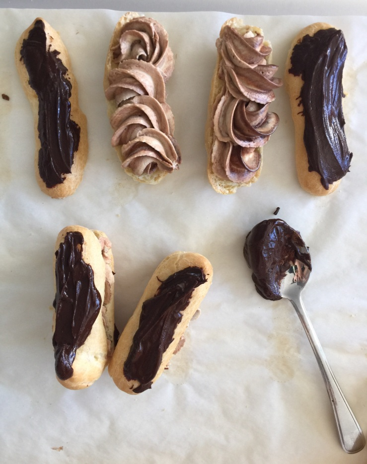 Piping the mocha cream on each eclair & spooning the chocolate on top.